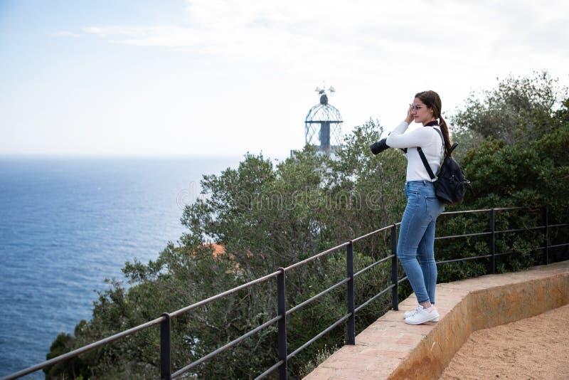 Femme prenant la photo de la plage du clou avec le phare brouillé sur le fond image libre de droits