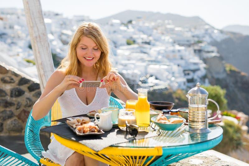 Femme prenant la photo de son petit déjeuner avec le téléphone portable image libre de droits