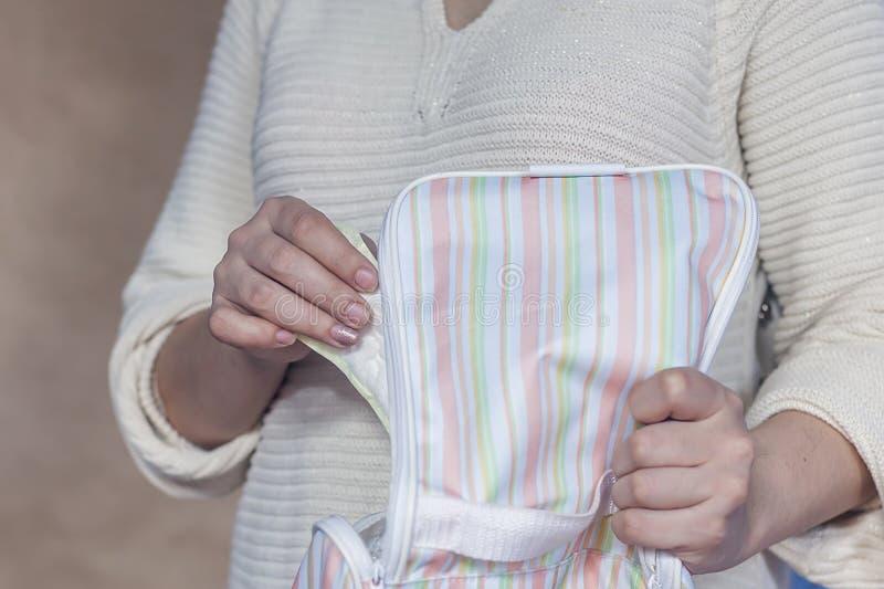 Femme prenant la protection menstruelle de son sac à main photos stock