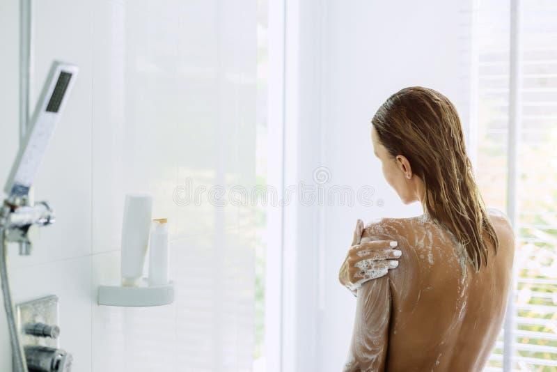 Femme prenant la salle de bains pendant le matin photographie stock libre de droits