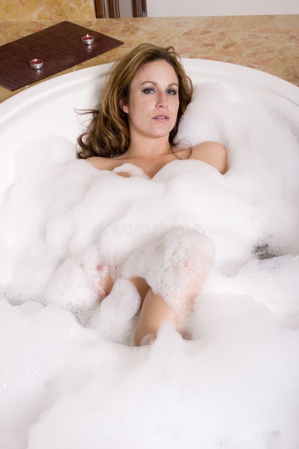 Femme prenant le bain de bulle image stock