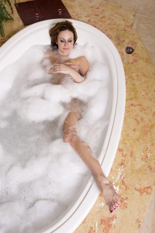 Femme prenant le bain de bulle images libres de droits