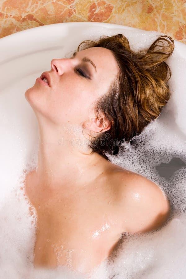 Femme prenant le bain de bulle photographie stock