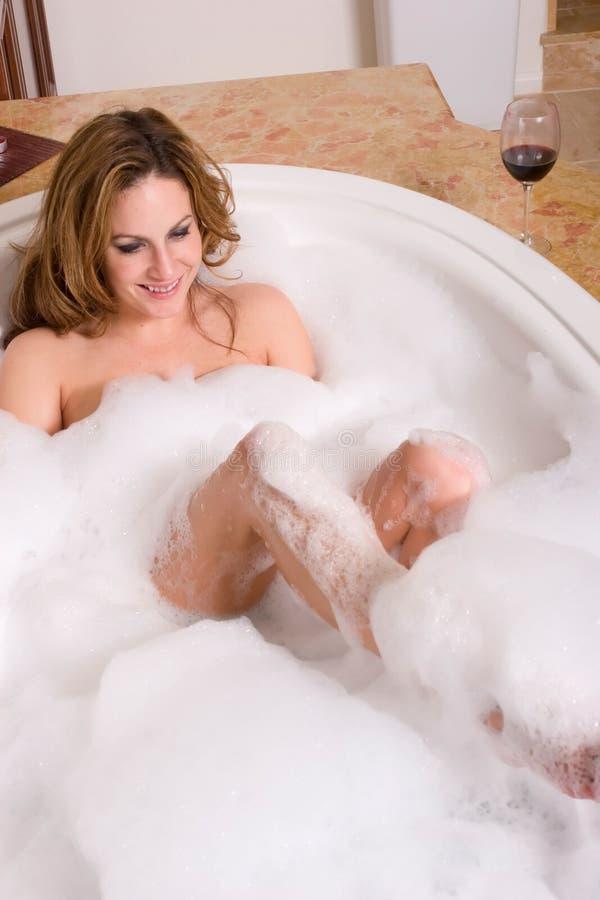 Femme prenant le bain de bulle images stock