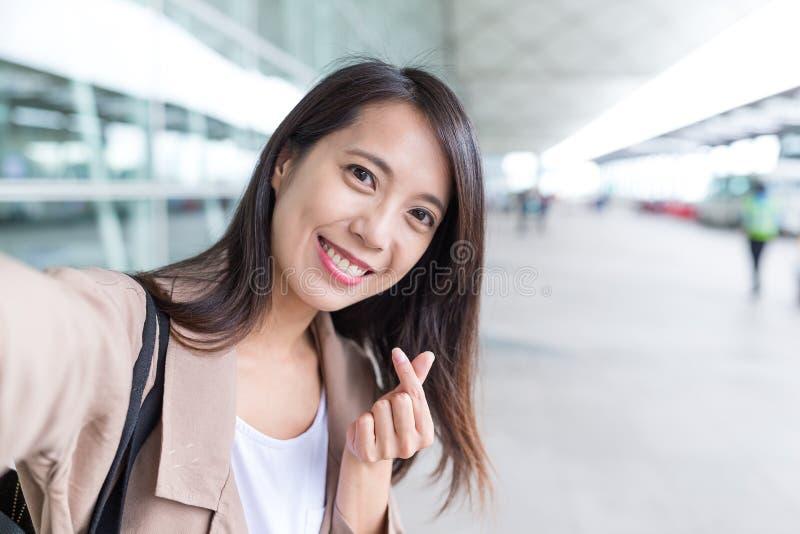 Femme prenant le selfie avec le geste coréen de doigt de coeur de style photo libre de droits