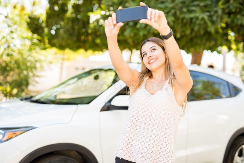 Femme prenant le selfiew avec sa nouvelle voiture image libre de droits