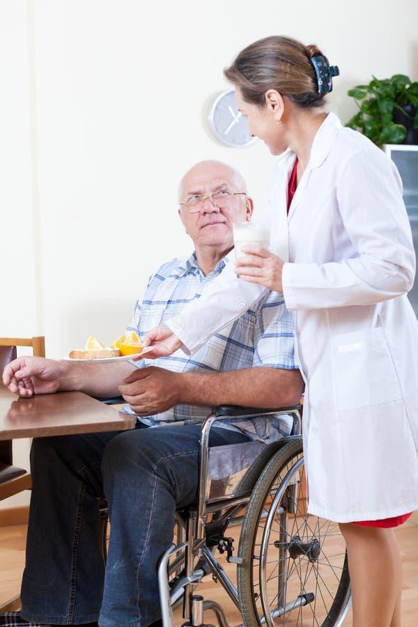 Femme prenant soin de l'homme dans le fauteuil roulant images libres de droits