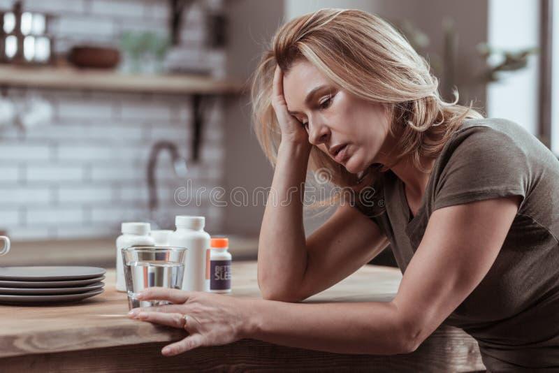 Femme prenant trop de comprimés somnifères pensant au suicide photos stock