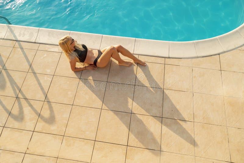 Femme prenant un bain de soleil par la piscine photos stock