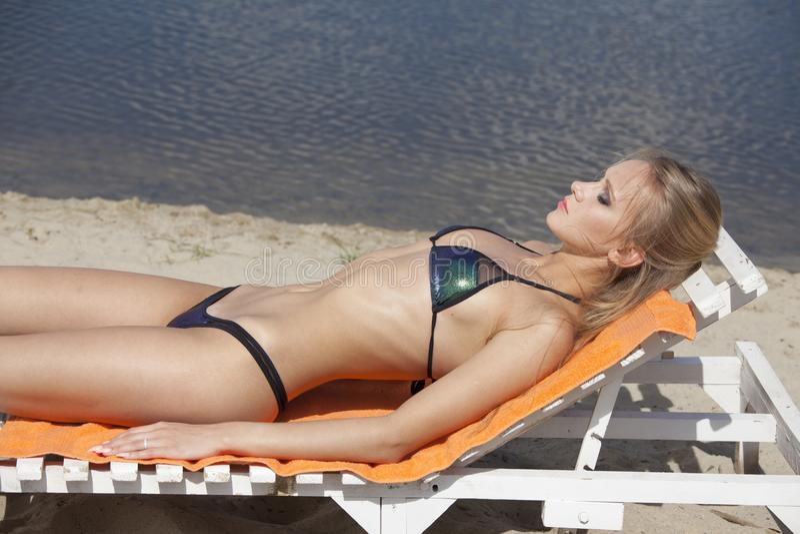 Femme prenant un bain de soleil sur la chaise photographie stock libre de droits