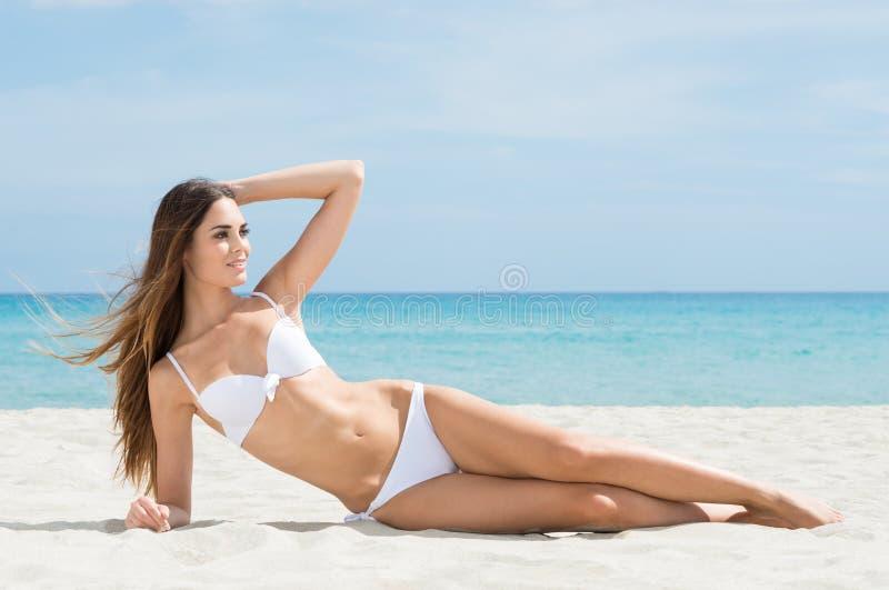Femme prenant un bain de soleil sur la plage photographie stock libre de droits