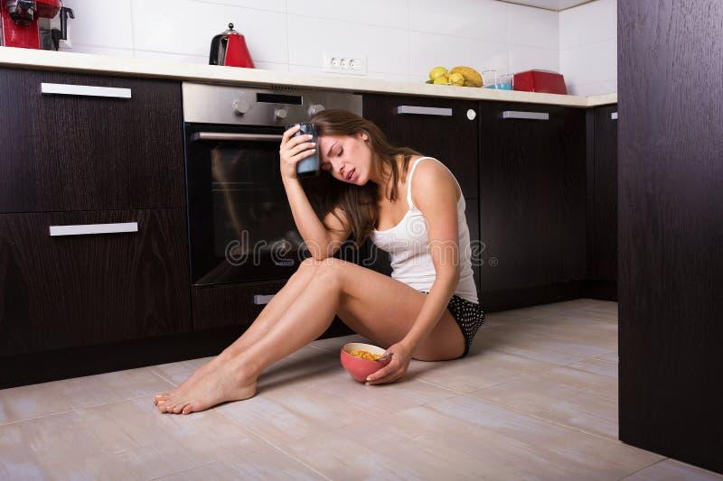 Femme prenant un petit déjeuner à sa cuisine images stock