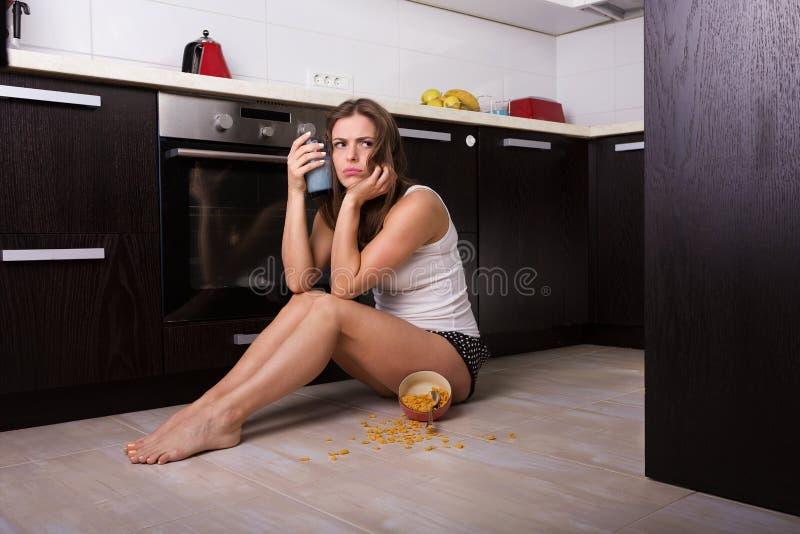 Femme prenant un petit déjeuner à sa cuisine photographie stock libre de droits