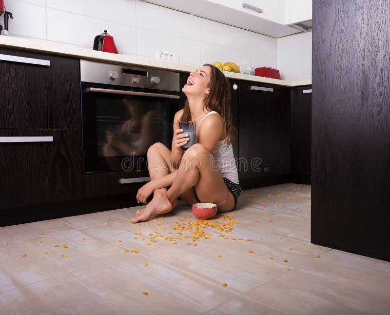 Femme prenant un petit déjeuner à sa cuisine image libre de droits