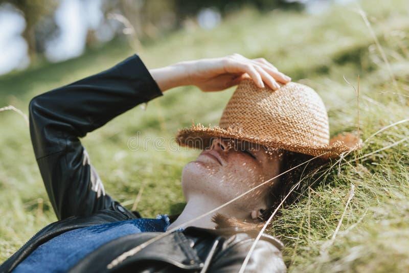 Femme prenant un petit somme sur l'herbe photographie stock