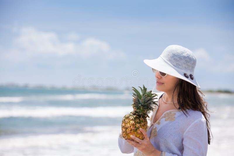 Femme prenant un verre tropical à la plage paradisiaque et tropicale dans une belle journée ensoleillée photographie stock