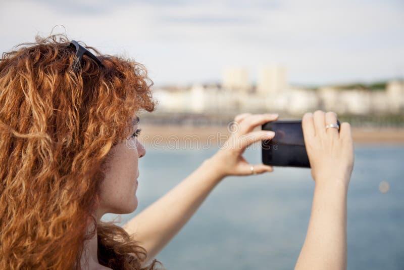 Femme prenant une photo photo stock