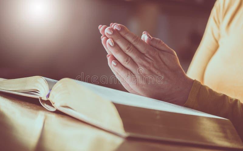 Femme priant avec ses mains au-dessus de la bible photo libre de droits