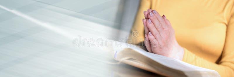 Femme priant avec ses mains au-dessus de la bible Drapeau panoramique images stock