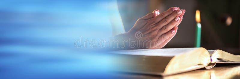 Femme priant avec ses mains au-dessus de la bible, lumi?re dure Drapeau panoramique photographie stock libre de droits