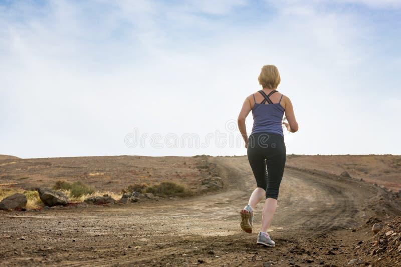 Femme pulsant sur le chemin de terre photo stock
