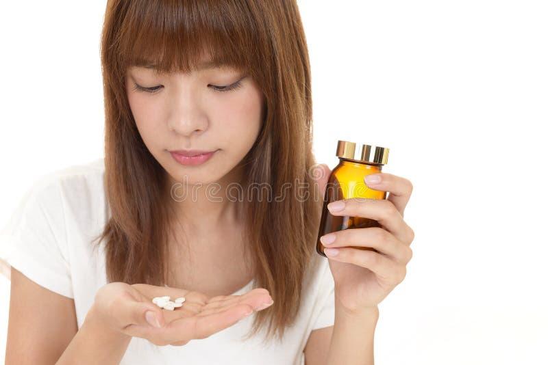 Femme qui boit des suppl?ments image stock