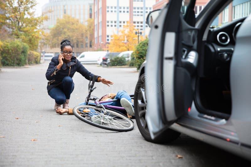 Femme r?clamant l'aide pr?s du cycliste inconscient se trouvant sur la rue images stock
