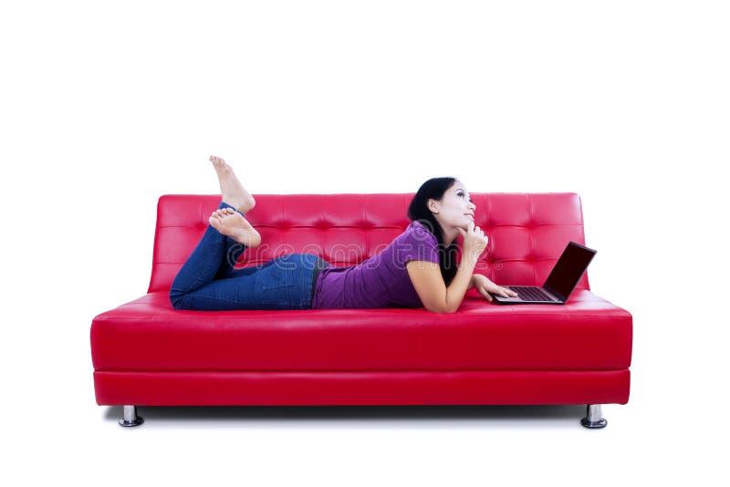Femme réfléchie avec l'ordinateur portable sur le divan images stock