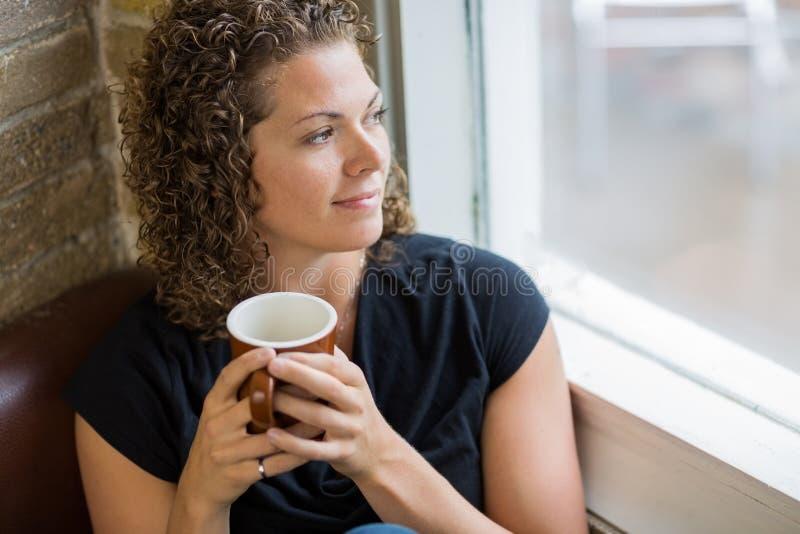 Femme réfléchie avec la tasse de café en café photographie stock libre de droits