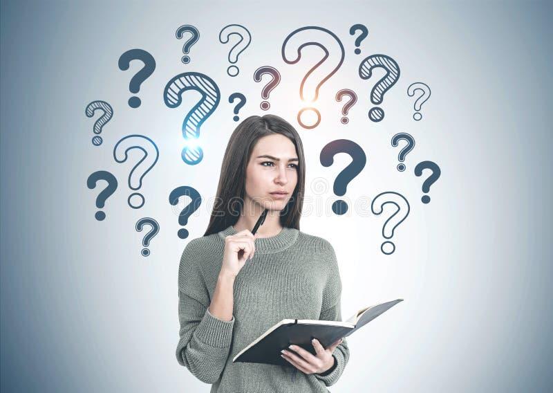 Femme réfléchie avec le carnet, points d'interrogation image stock