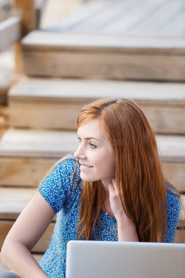 Femme réfléchie avec son ordinateur portable photographie stock libre de droits