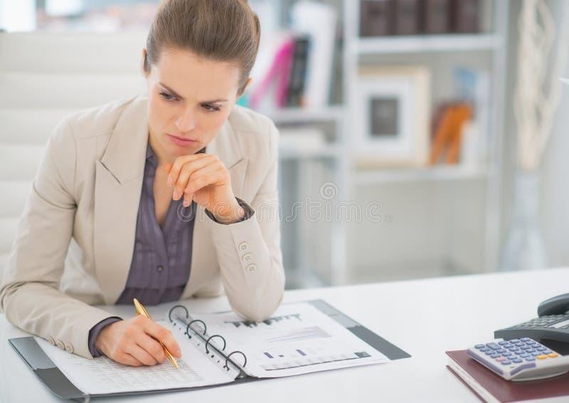 Femme réfléchie d'affaires travaillant avec des documents photo stock