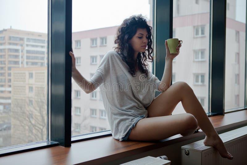 Femme réfléchie en appartement de ville photo stock