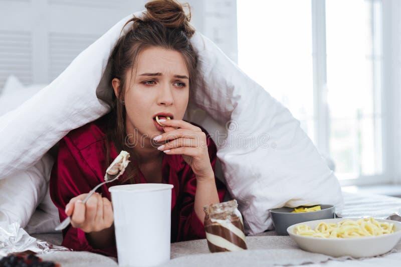 Femme réfléchie mangeant des puces pensant à l'avenir photos libres de droits