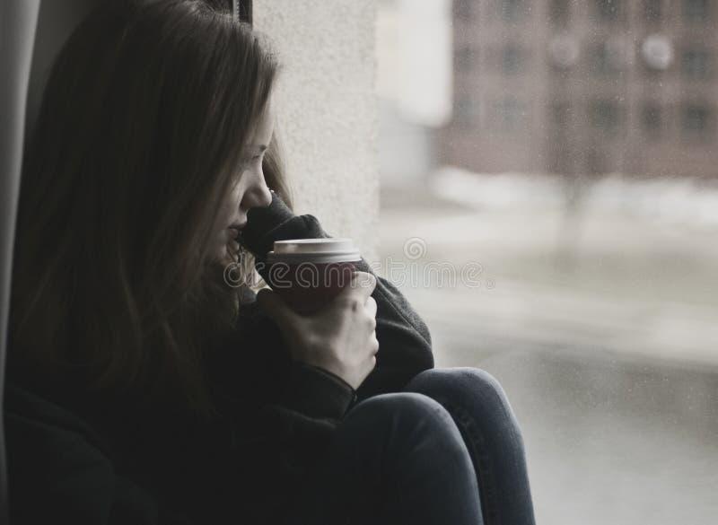 Femme réfléchie regardant la fenêtre photo libre de droits