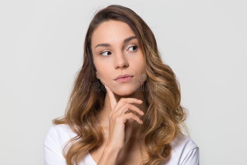 Femme réfléchie regardant le doute se sentant loin d'isolement sur le fond blanc images stock