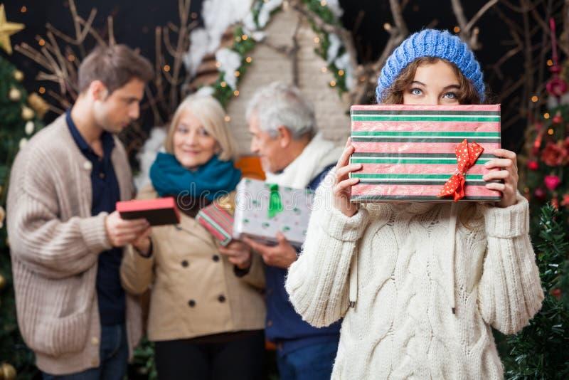 Femme réfléchie tenant le cadeau de Noël avec images stock