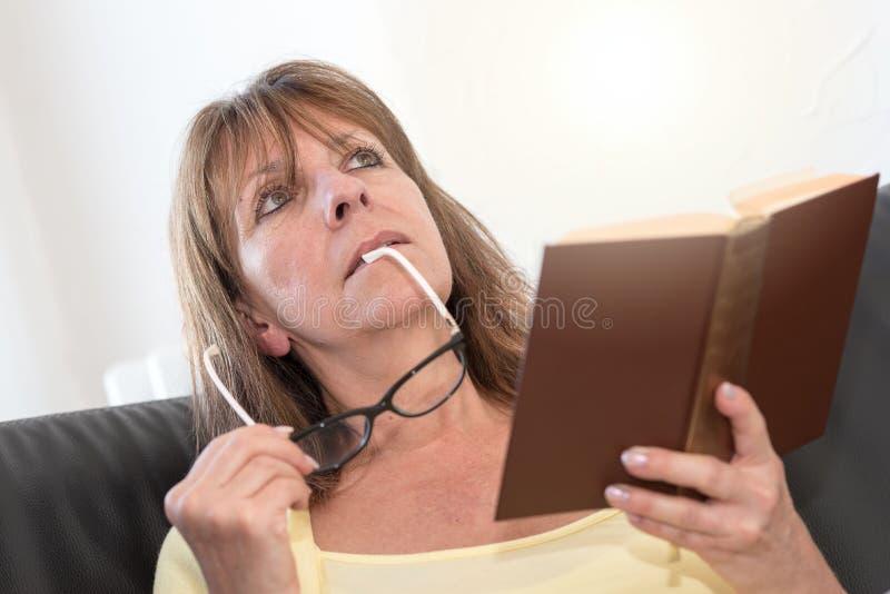 Femme réfléchie tenant ses verres et lisant un livre images stock