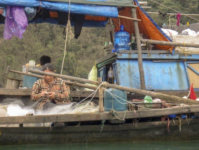 Femme réparant des filets dans le bateau de pêche dans la baie long Vietnam d'ha photo libre de droits