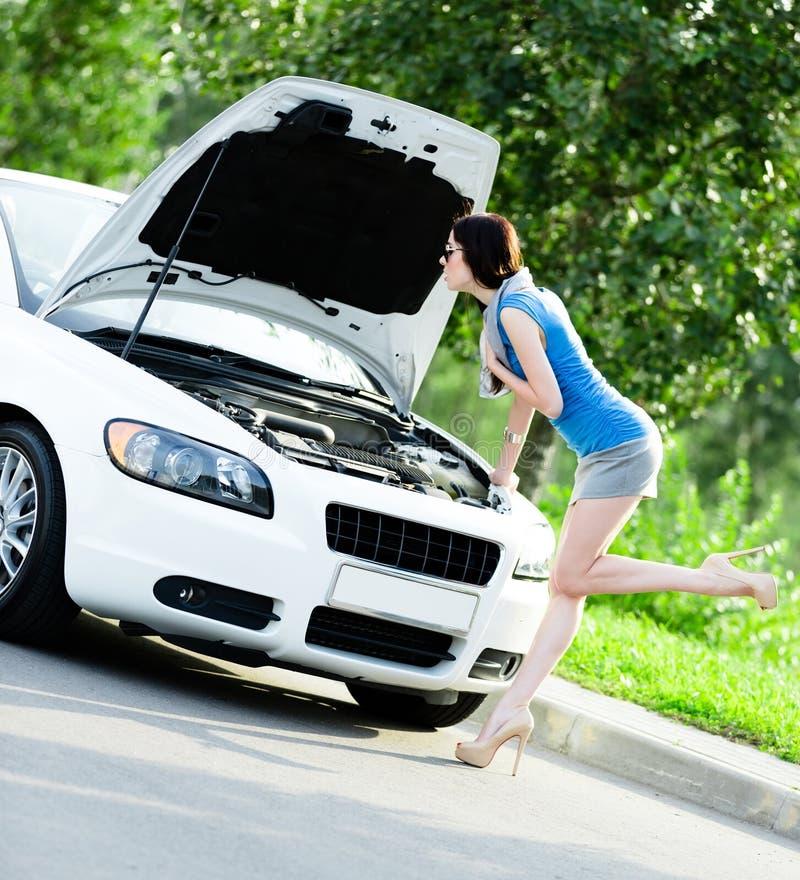 Femme réparant le véhicule blanc cassé photographie stock libre de droits