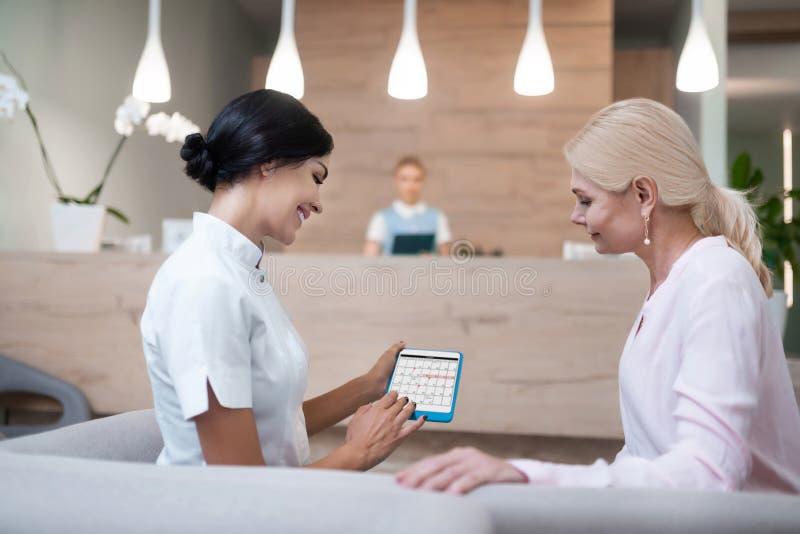 Femme réparant une réunion avec son dentiste image stock
