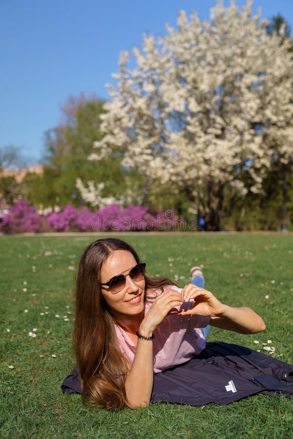 Femme réussie d'affaires montrant le signe d'amour de coeur avec des mains se trouvant sur l'herbe appréciant le temps libre de l photographie stock libre de droits