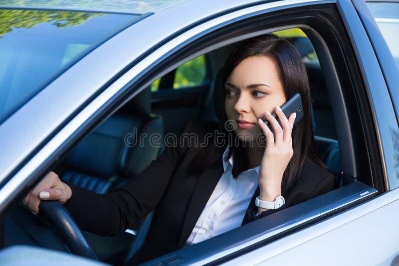 Femme réussie d'affaires parlant sur le smartphone dans sa voiture photos libres de droits
