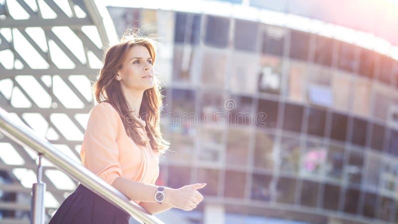 Femme réussie d'affaires se tenant sur le balcon du bureau et des regards modernes dans la distance photographie stock libre de droits