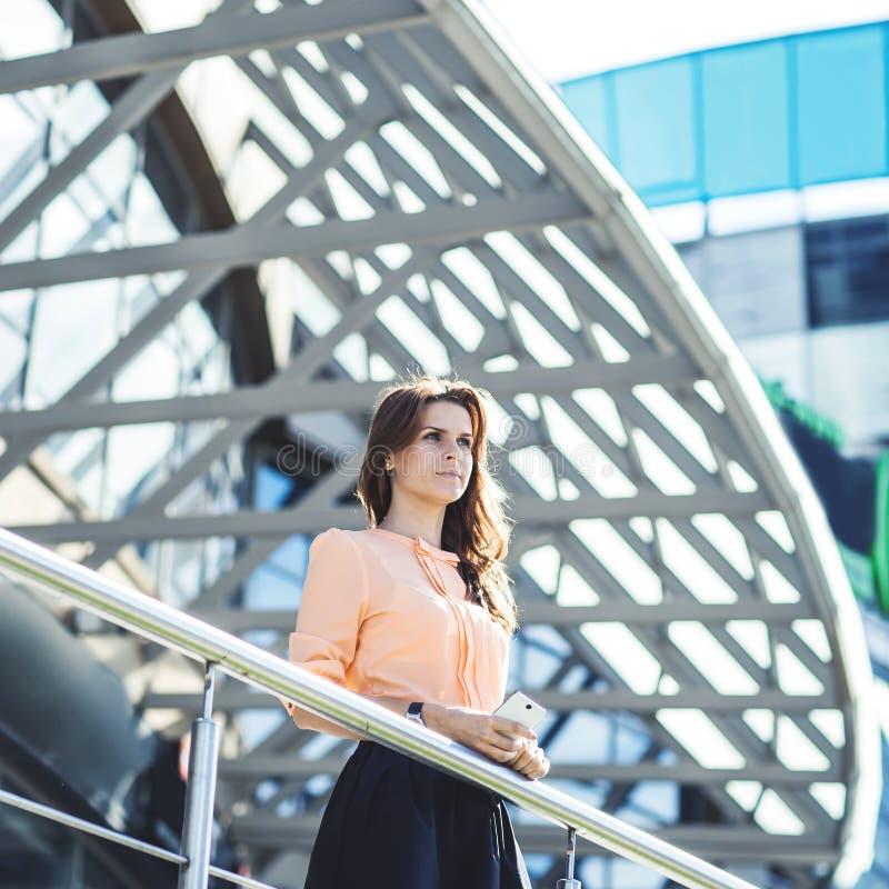 Femme réussie d'affaires se tenant sur le balcon du bureau et des regards modernes dans la distance image libre de droits
