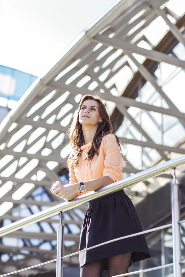 Femme réussie d'affaires se tenant sur le balcon du bureau et des regards modernes dans la distance photo stock