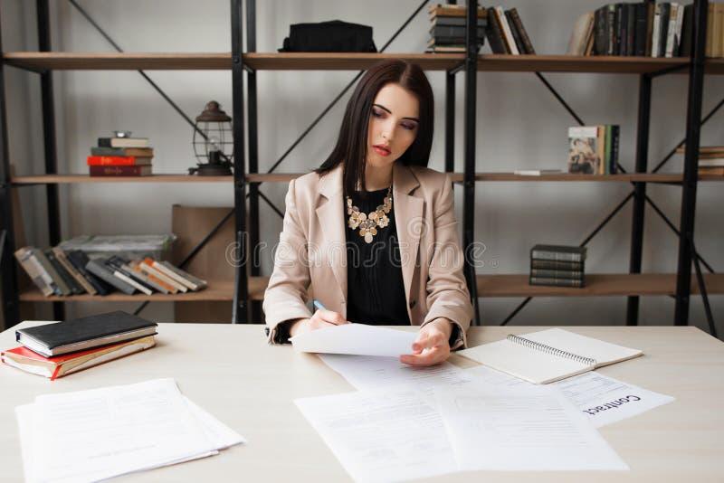 Femme réussie d'affaires vérifiant la documentation photo libre de droits