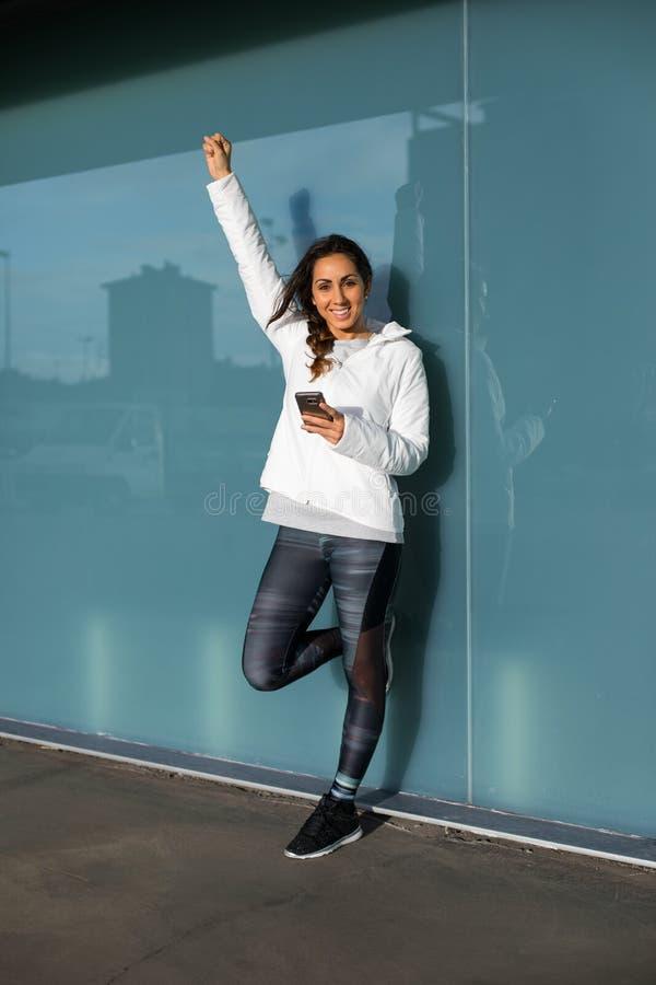 Femme réussie de forme physique à l'aide du smartphone images libres de droits
