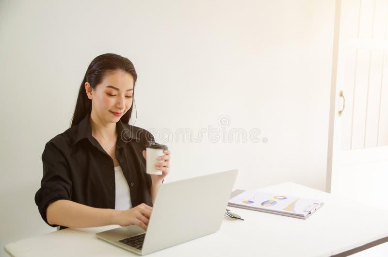 Femme réussie mûre d'affaires regardant l'ordinateur portable tandis qu'à la maison dans l'espace de travail de bureau image stock