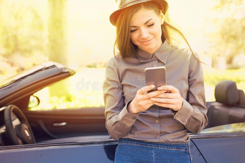 Femme réussie se tenant prêt son service de mini-messages de voiture au téléphone portable photo stock